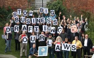 """Das Bild zeigt Mitglieder der Allianz für Lobbytransparenz und ethische Regeln (ALTER-EU). Sie fordern, dass Unternehmenslobbyisten nicht an unseren Gesetzen mitschreiben (""""stop big business drafting our laws."""")."""