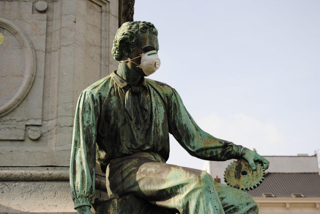 Das Foto zeigt eine Statue mit Atemschutzmaske auf dem Platz vor dem Europäischen Parlament.