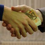 Ein Geldbündel wechselt per Händedruck den Besitzer